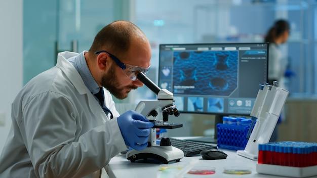 Ученый-мужчина смотрит под микроскопом в лаборатории медицинских разработок, вводя данные в компьютер. специалисты, занимающиеся медициной, биотехнологическими исследованиями в передовой фармацевтической лаборатории.