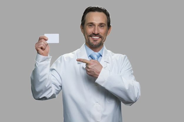 Male scientist pointing on business card. medical worker showing business card and looking at camera against gray background.