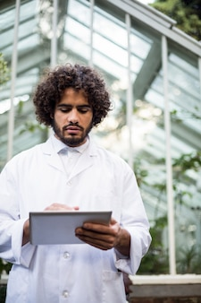 Male scientist using tablet computer outside greenhouse