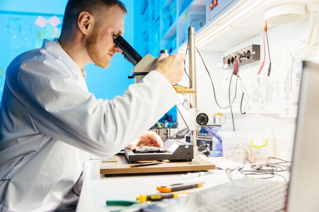 Male scientist wearing robe uses microscope for examining and soldering components on electronic circuit board