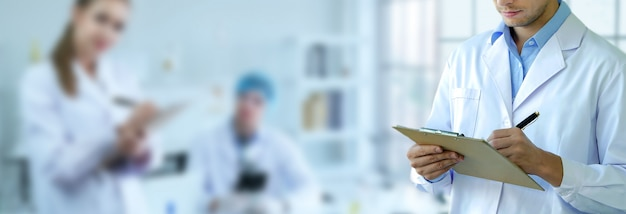 남성 과학자는 짧은 메모를 작성하고 팀과 실험실에서 작업