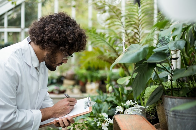 Male scientist writing in clipboard while examining plants