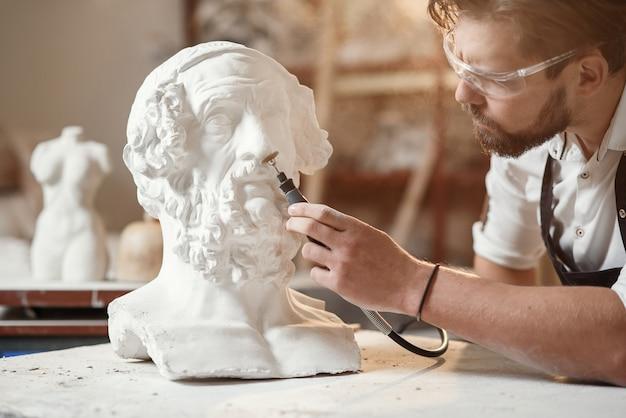 Мужской скульптор ремонтирует гипсовую скульптуру головы женщины на рабочем месте в творческой художественной мастерской.