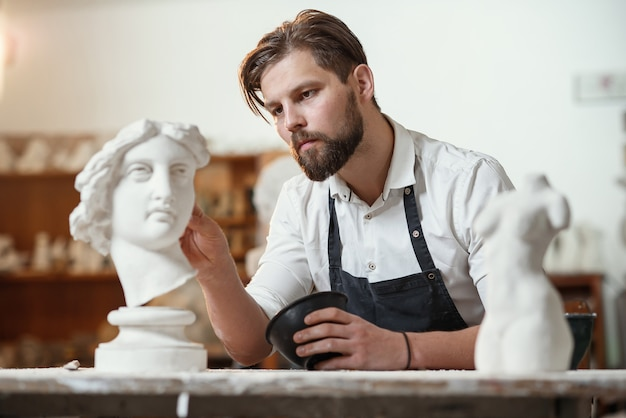 Male sculptor repairing gypsum sculpture of woman's head at the working place in the creative artistic studio.