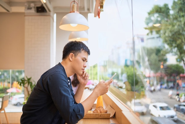 男性はジュースと甘いデザートを持ってテラスカフェに座っている間、スマートフォンを介してインターネットのウェブサイトで必要な情報を検索します