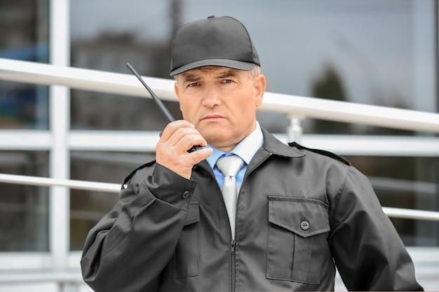 屋外で携帯ラジオを使用する男性警備員