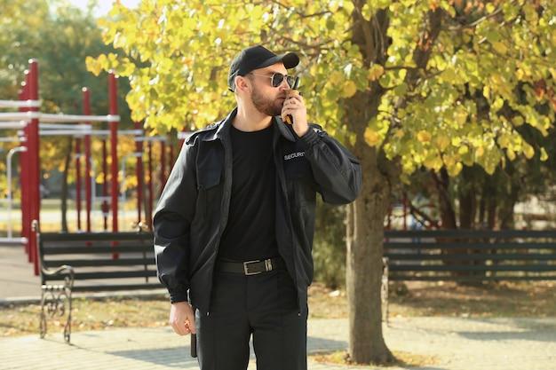 屋外で携帯無線送信機を備えた男性警備員