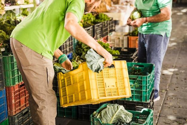 男性の売り手が市場で野菜の木枠を手配