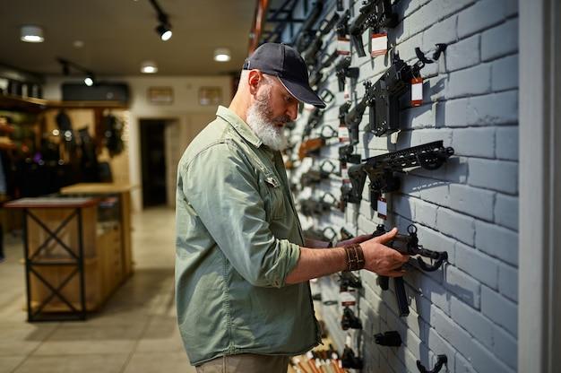 銃の店でライフルを持ったショーケースの男性売り手。武器屋のインテリア、弾薬と弾薬の品揃え、銃器の選択、射撃の趣味とライフスタイル、護身術