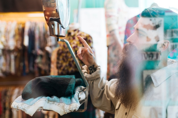 Male seller checking fabric weight on scales at clothing shop seen through glass