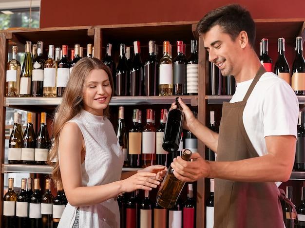Продавец-мужчина помогает женщине выбрать вино в магазине