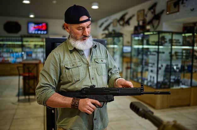 男性の売り手は銃の店で自動小銃を持っています。武器屋のインテリア、弾薬と弾薬の品揃え、銃器の選択、射撃の趣味とライフスタイル、護身術