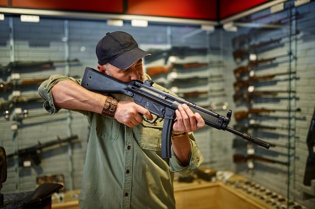 男性の売り手は銃の店で自動小銃を保持します