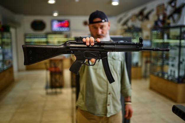 男性の売り手は銃の店で自動小銃を示しています。武器屋のインテリア、弾薬と弾薬の品揃え、銃の選択、射撃の趣味とライフスタイル、護身術
