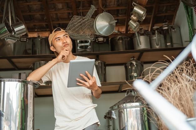 Продавец-мужчина стоит и думает о маркетинговой стратегии при использовании планшета для интернет-магазина в магазине