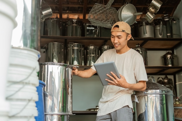 Продавец-мужчина стоит возле большой сковороды, используя планшет для проверки интернет-магазина в магазине бытовой техники