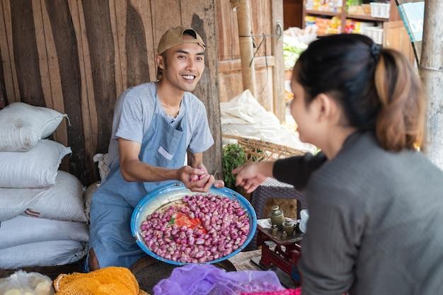 Продавцы-мужчины забирают лук-шалот, чтобы обслуживать покупательницу у овощного прилавка