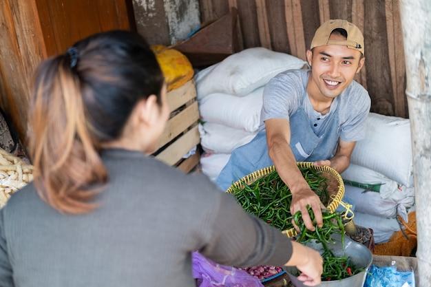 Продавцы-мужчины, берущие зеленый перец чили, обслуживают покупателей-женщин на овощных прилавках