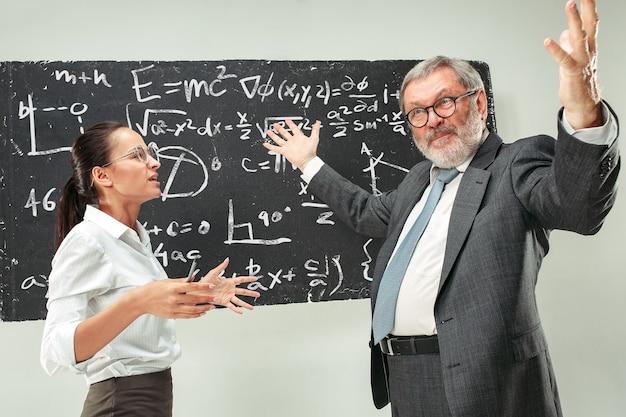 Старший профессор мужского пола и молодая студентка против доски в классе. концепция человеческих эмоций. кавказские модели. образование, колледж, университет, лекция, школа, концепции обучения