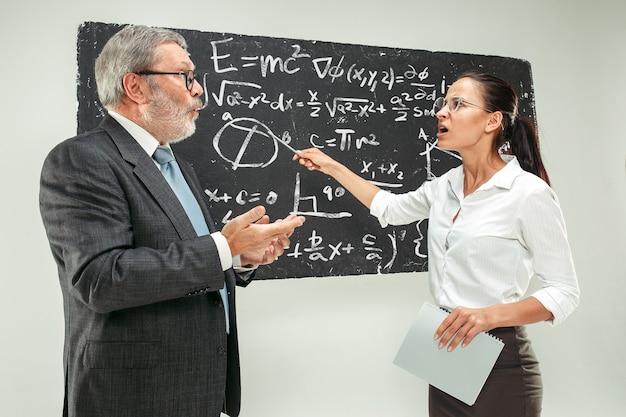 教室で黒板に反対する男性の上級教授と若い女性の学生。人間の感情の概念。白人モデル。教育、大学、大学、講義、学校、学習の概念