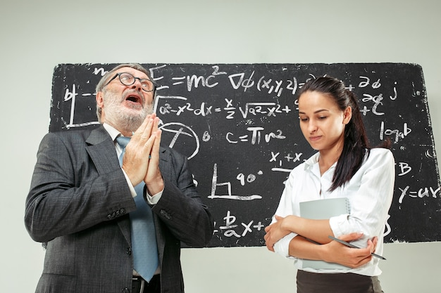 Male senior professor and young female student against chalkboard in classroom. human emotions concept. caucasian models. education, college, university, lecture, school, learning concepts