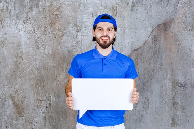 Agente di servizio maschio in uniforme blu che tiene una scheda informativa rettangolare.