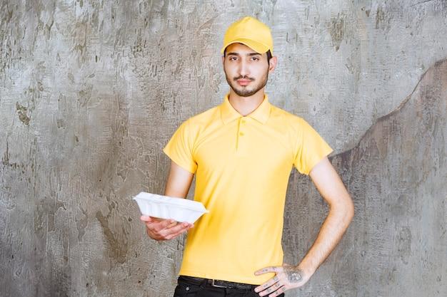 白いテイクアウトボックスを保持している黄色の制服を着た男性サービスエージェント。