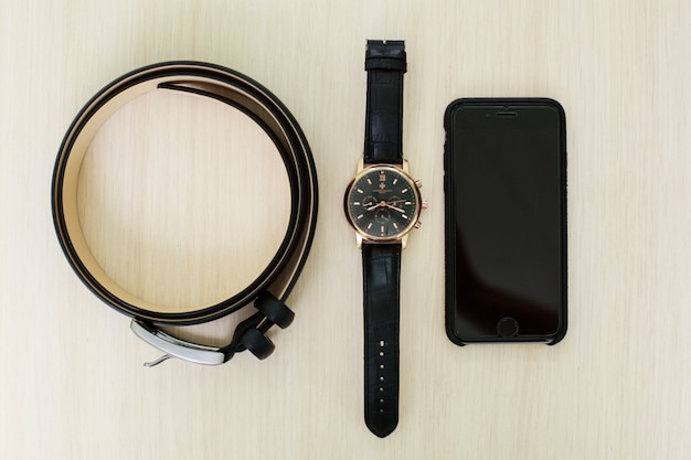 Male set - men's  black leather belt on trousers, wristwatch and phone close up. set of stylish men's accessories. groom accessories. details of business man's clothing