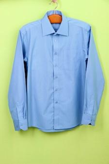 Мужская рубашка на вешалке на стене