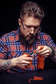 Мужской сапожник, режущий кожаный текстиль в мастерской.