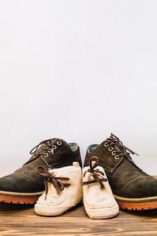 Le scarpe maschii si avvicinano agli stivali del bambino sul bordo di legno