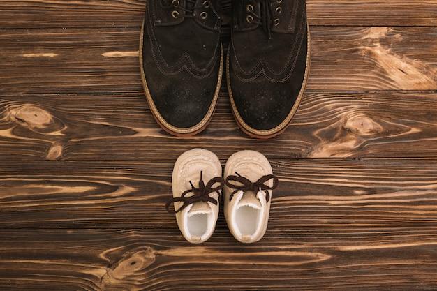 Scarpe maschili vicino a stivali da bambino
