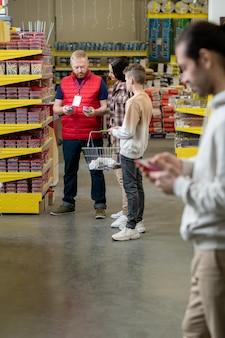 Продавец-консультант мужского пола, консультирующий потребителей в современном хозяйственном супермаркете