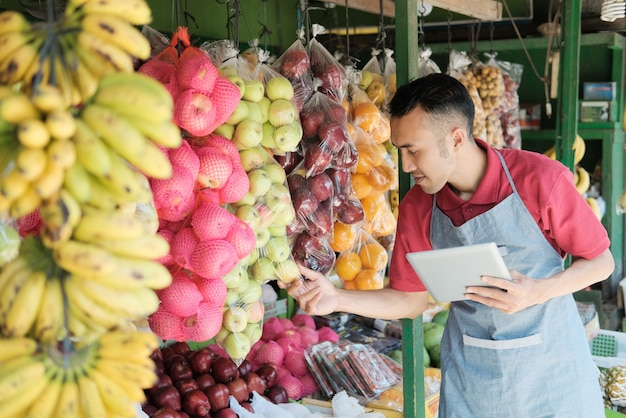 A male shop owner holding a digital tablet while observing fresh fruit in a fruit shop