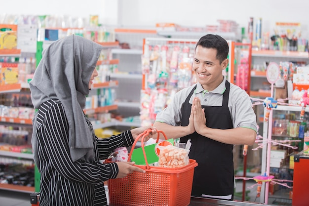Male shopkeeper or cashier welcoming customer