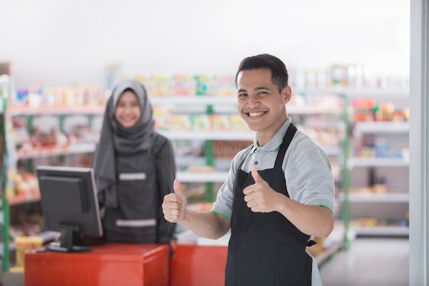 Male shopkeeper showing thumb up