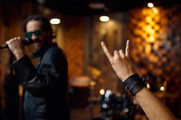 マイクの男性歌手、ステージで演奏する音楽。ロックバンドの演奏またはガレージでの繰り返し、楽器を持った男、ライブサウンドパフォーマー