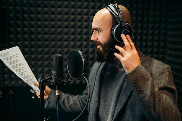 Male singer in headphones songs in audio recording studio.