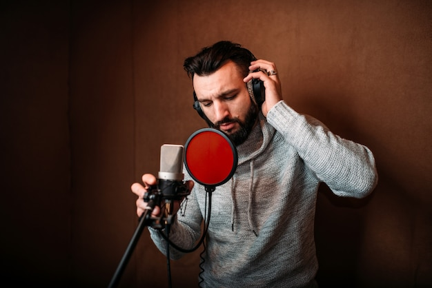 Male singer recording a song in music studio. vocalist in headphones against microphone.