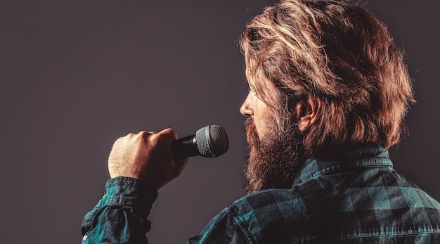 Male singing with a microphones. man with a beard holding a microphone and singing. bearded man in karaoke sings a song into a microphone.