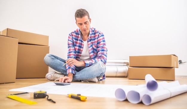 男性は、引っ越し、計画、計算を行った後、新しい家の床に座ります。