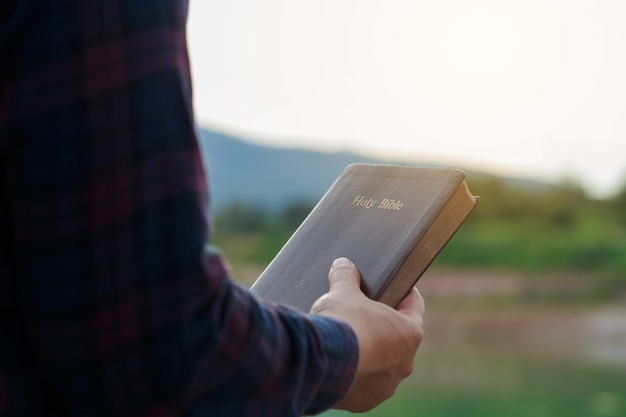 자연 배경으로 그의 손에 성경을 들고 앉아 있는 남성. 일요일 독서, 성경