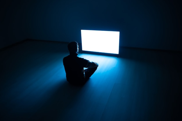 The male sitting in the dark room in front of a white screen
