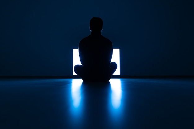 The male sitting on the floor in front of the television in the dark room