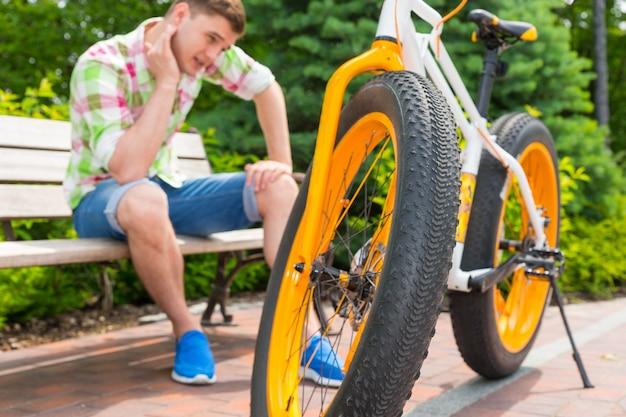 자전거 근처 벤치에 앉아 슬픈 표정으로 앉아 있는 남성, 아름다운 녹색 공원에서 바퀴에 집중