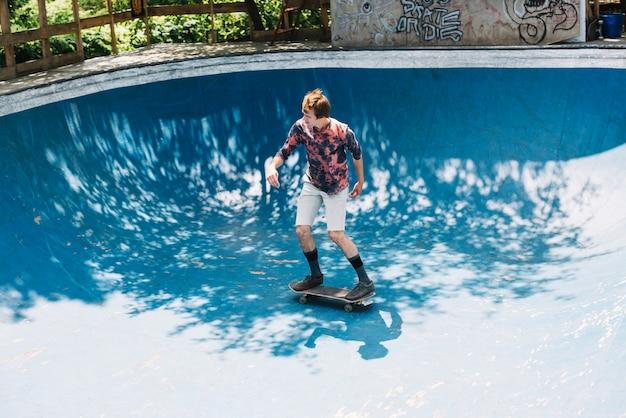 Skateboarder maschio in sella alla rampa
