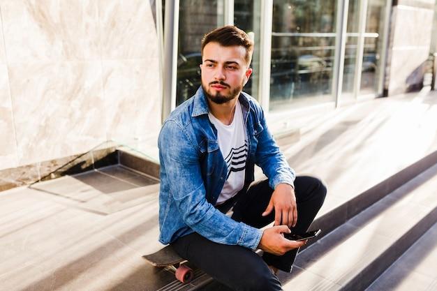 スマートフォンでスケートボードに座っている男性スケートボーダー