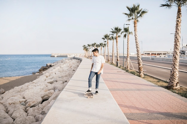 Male skateboarder with a skateboard standing by sea