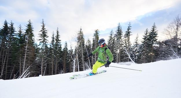 男性のスキーヤーのバックパッカーが、砂漠の森が茂ったスロープでスキーをする極値フリーライド。雪山でのカービングターン技。