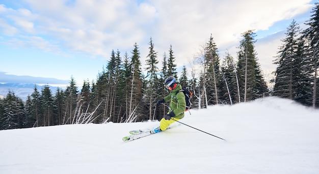 スキー砂漠の樹木が茂った斜面での男性スキーヤーバックパッカー極値フリーライディングスキー